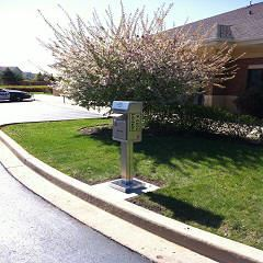 Drop Box in Front of a Flowering Bush Located at 5000 Sleepy Hollow Road